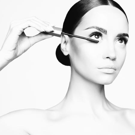 美しい若い女性の白黒スタジオ ファッション写真は、マスカラーを適用されます。
