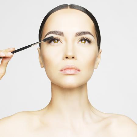 Studio fashion photo of beautiful young lady applied mascara.