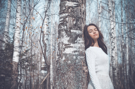 Outdoor fashion photo of young beautiful lady in a birch forest Standard-Bild