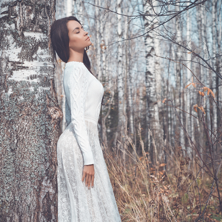 russian: Outdoor fashion photo of young beautiful lady in a birch forest Stock Photo