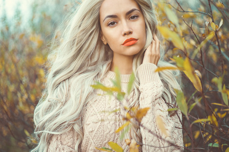 light hair: Outdoor fashion photo of young beautiful lady surrounded autumn leaves