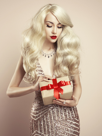 Fashion studio photo of luxury blonde with Christmas gift. Merry Christmas. Happy New Year