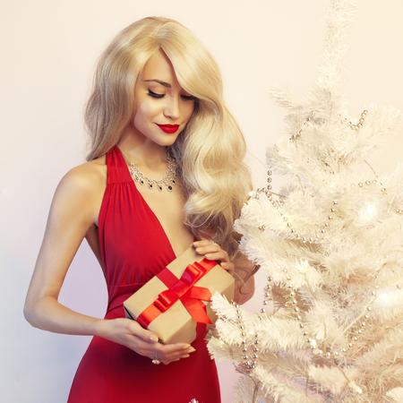navidad elegante: Moda estudio de la foto de la rubia de lujo con el regalo de Navidad. Feliz Navidad. Feliz año nuevo