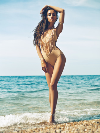 Outdoor fashion portrait of tanned lady in sexual swimsuit posing at beach