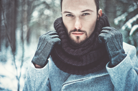 Outdoor portrait of handsome man in coat and scurf. Casual winter fashion Foto de archivo