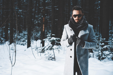 Outdoor portrait of handsome man in coat and scurf. Casual winter fashion Archivio Fotografico