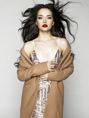 brunet: Beautiful sexy brunette model in fashion clothes posing in studio. Wearing coat, evening dress