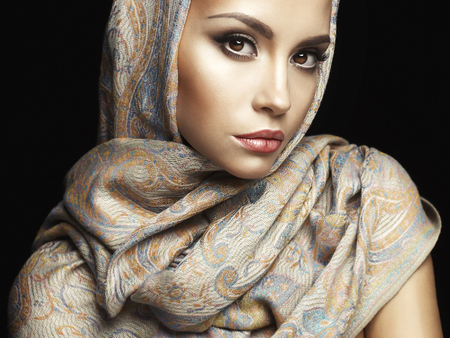 ladies: Studio fashion portrait of beautiful lady wrapped in a orient shawl Stock Photo