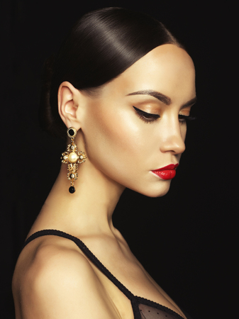 red lip: Fashion portrait of young beautiful lady with earring on black background Stock Photo