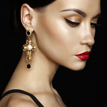 Fashion studio portrait of young beautiful lady with earring on black background Foto de archivo