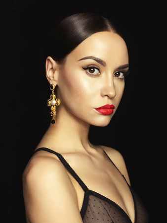 Fashion portrait of young beautiful lady with earring on black background Фото со стока