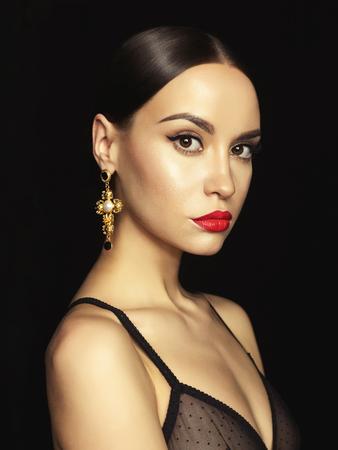 Retrato de la señora hermosa joven con el pendiente en el fondo negro