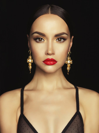 Fashion portrait of young beautiful lady with earring on black background Imagens