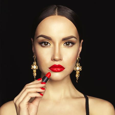 red lips: Moda foto de estudio de la hermosa dama joven aplicar el lápiz labial rojo. maquillaje de la cara perfecta. Belleza y joyas