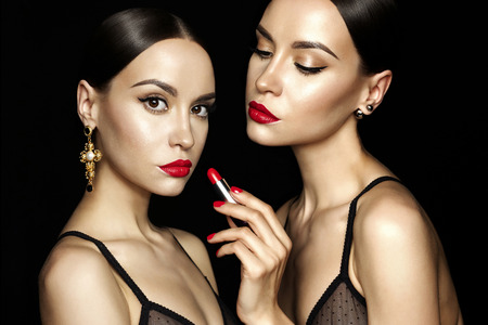 Fashion studio photo of two beautiful young ladies with red lipstick. Perfect face makeup. Beauty and jewelry Stock Photo
