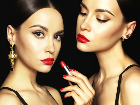 portrait studio: Fashion studio photo of two beautiful young ladies with red lipstick. Perfect face makeup. Beauty and jewelry Stock Photo