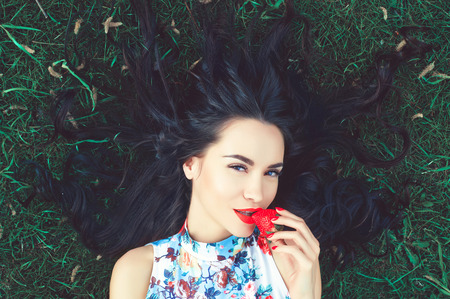summer nature: Outdoor fashion photo of beautiful young lady on grass with strawberry in mouth