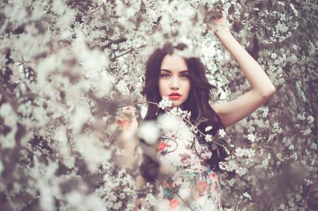 summer dress: Outdoors fashion photo of beautiful young lady in the garden of cherry blossoms