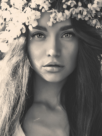 Black and white portrait of beautiful romantic lady in a wreath of apple trees