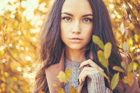 Outdoor photo de mode de jeunes belle dame entourée de feuilles d'automne Banque d'images - 64495904