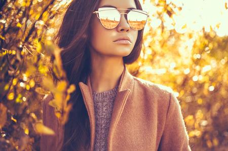 Openlucht modefoto van jonge mooie dame omringde de herfstbladeren