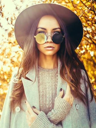 젊은 아름 다운 숙 녀의 야외 패션 사진 둘러싸인 단풍