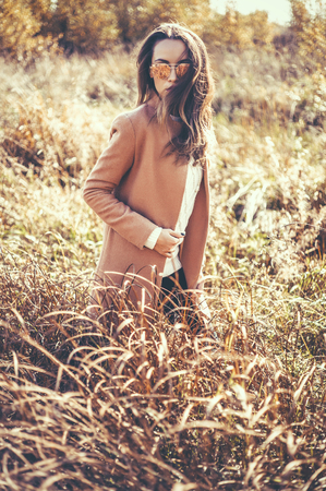 spica: Outdoor fashion photo of young beautiful lady in autumn landscape