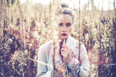 Outdoor fashion photo of young beautiful lady in autumn landscape with dry flowers