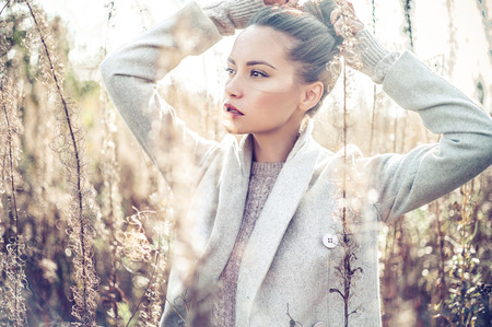young lady: Outdoor fashion photo of young beautiful lady in autumn landscape with dry flowers