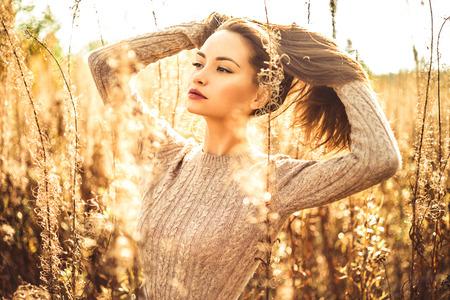 乾燥した花秋風景の中の若い美しい女性の屋外のファッション写真