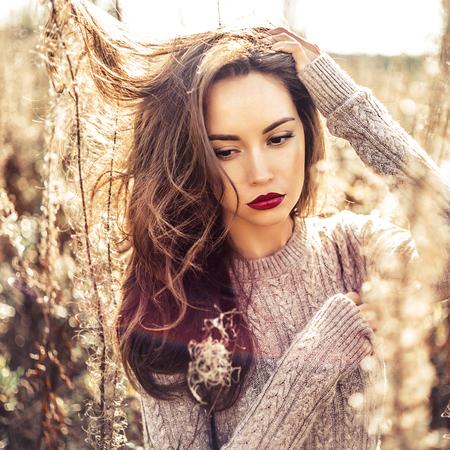 atmosfera: Foto de la moda al aire libre de la joven y bella dama en el paisaje de otoño con las flores secas