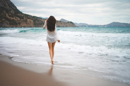 Outdoor photo of beautiful young woman walking at the sea