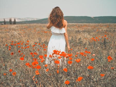 양 귀 비 필드에서 아름 다운 젊은 여자의 야외 사진