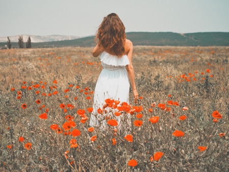 Outdoor photo of beautiful young woman in the poppy field Stock Photo
