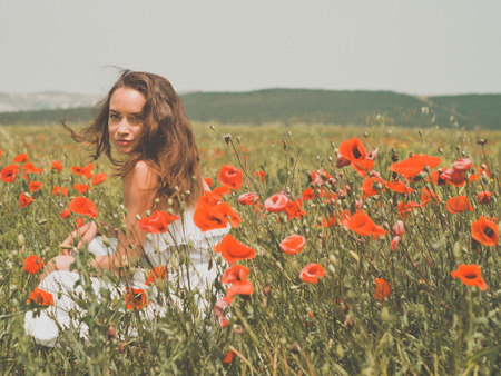 outdoor photo: Outdoor photo of beautiful young woman in the poppy field Stock Photo