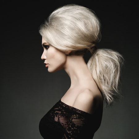 Fashion studio portrait of beautiful blonde woman with elegant hairstyle on black background