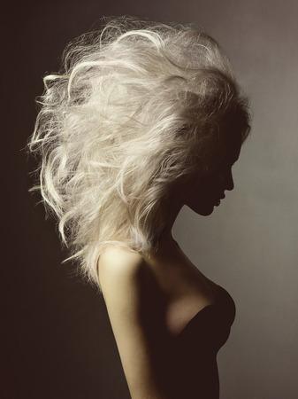 黒い背景にボリューム髪型の金髪美女のファッション スタジオ ポートレート 写真素材