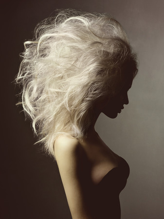 Fashion studio portrait of beautiful blonde woman with volume hairstyle on black background Stock Photo