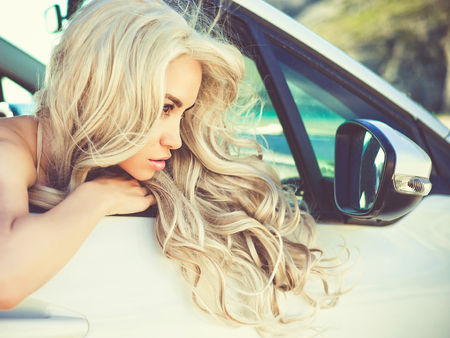 Atmospheric outdoors fashion portrait of beautiful blonde in car on the beach Stock Photo