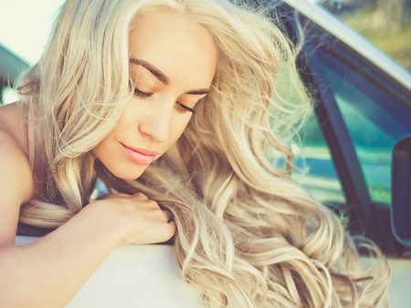 Atmospheric outdoors fashion portrait of beautiful blonde in car on the beach Standard-Bild