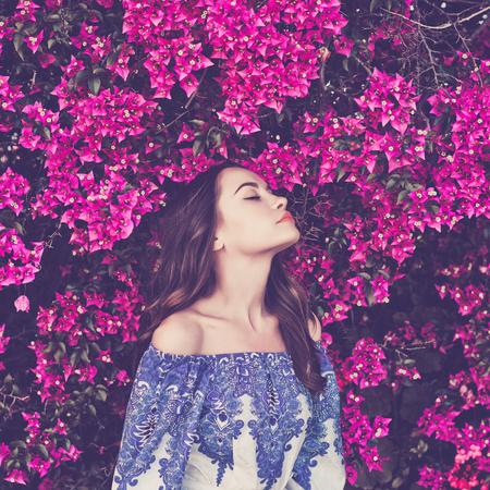 花に囲まれた美しい若い女性の屋外のファッション写真 写真素材