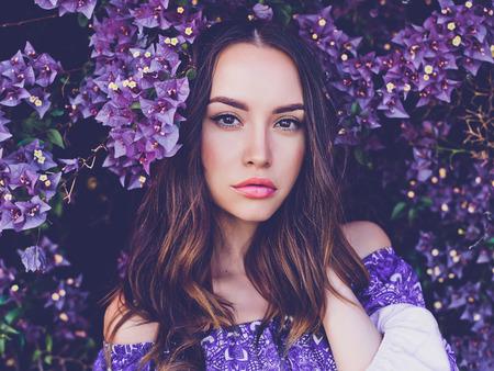 Outdoor mode foto van mooie jonge vrouw, omringd door bloemen