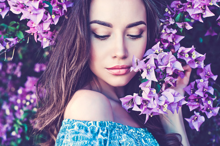 Outdoor fashion photo of beautiful young woman surrounded by flowers Banco de Imagens - 64495985