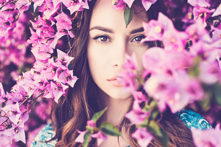 Outdoor fashion photo of beautiful young woman surrounded by flowers