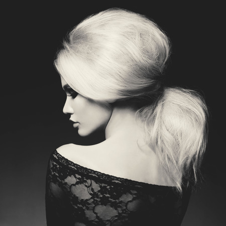 Black and white fashion studio portrait of beautiful blonde woman with elegant hairstyle on black background Foto de archivo