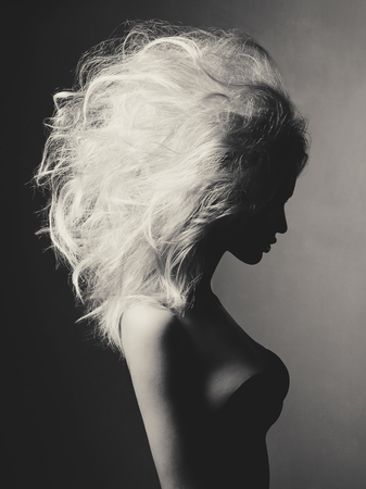 Black and white fashion studio portrait of beautiful blonde woman with volume hairstyle on black background