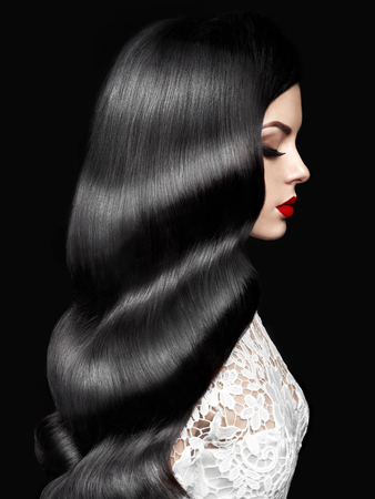 Fashion studio photo of beautiful model girl brunette with long curled hair and red lips. Hairstyle Hollywood wave. Wedding image hairstyle. Perfect makeup