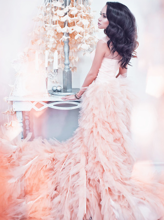 Fashionable portrait of beautiful lady in gorgeous couture dress in white interior. Holidays & Events. Evening dress. Princess dress