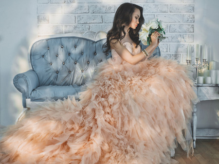 retro woman: Fashionable portrait of beautiful lady in gorgeous couture dress on sofa. Holidays & Events. Evening dress. Princess dress