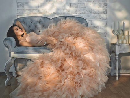 Fashionable portrait of beautiful lady in gorgeous couture dress on sofa. Holidays & Events. Evening dress. Princess dress